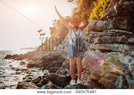 A Young Hipster Woman Hat And A Rukzak With Her Hands Up, Standing On Top Of A Cliff And Looking Sea