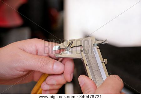 Mechanic Is Checking And Measuring Old Mechanic Yellow Screwdriver Size With Stainless Steel Caliper