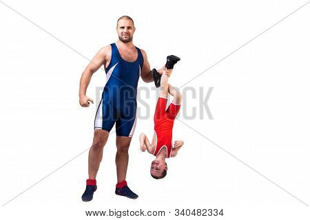 Men In Wrestling Tights And Wrestlers Holds The Foot Of A Wrestler Boy On A White Isolated Backgroun