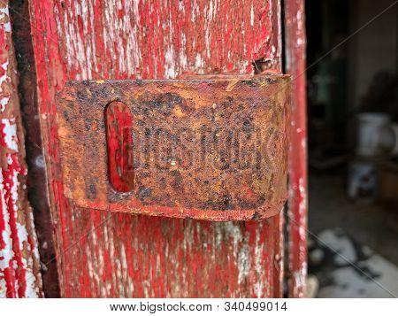 Rusty Lock Hinge On Door With Peeling Red Paint