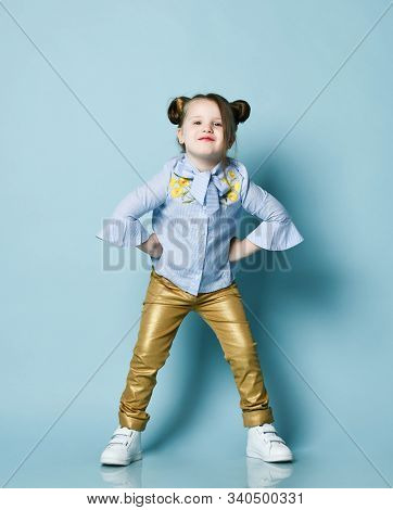 Playful Frolic Impish Kid Girl With Funny Buns And In Blue Shirt And Gold Leather Pants Is Cool Posi