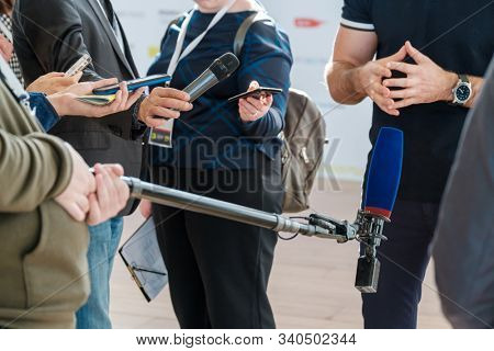 Journalists interview a politician, holding microphones and voice recorders