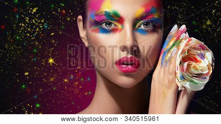 Beautiful Girl With Festive Bright Multi-colored Make Up  On The Face. Young Woman Dressed In Extrav