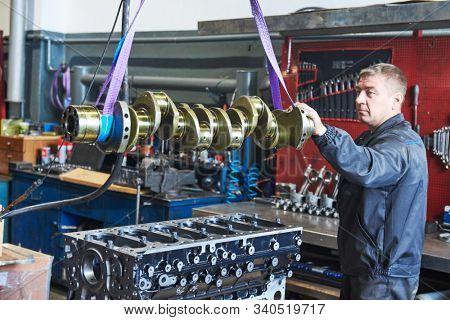 diesel truck engine repair service. Automobile mechanic installing crankshaft into engine