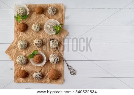 Energy Bites With Cocoa Powder, Sesame Seeds And Coconut Flakes On White Wooden Table, Top View With