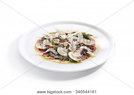 Beef carpaccio with mushrooms, parmesan, fresh arugula and fragrant oil on white restaurant plate isolated.Thin slices of raw veal or venison meat seasoned with vinegar closeup