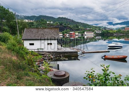 View From Samnanger To Samnangerfjorden Waters In Hordaland County, Norway. Old Wooden Poer And Two