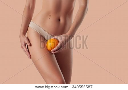 Slim Woman Is Holding Orange. Perfect Female Hips In Underwear W