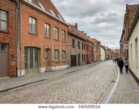 People Walking Along A Cobblestone Street In Bruges