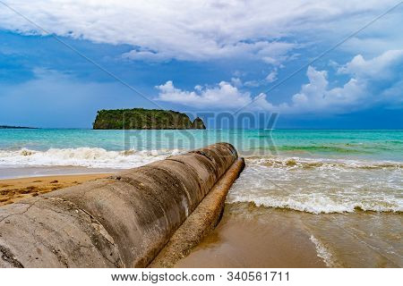 Cylindrical cement grey water/ storm water/ sewage/ sewer pipe outlet above ground from the sea shore into the ocean. Old dirty waste water irrigation management pipeline drainage. poster