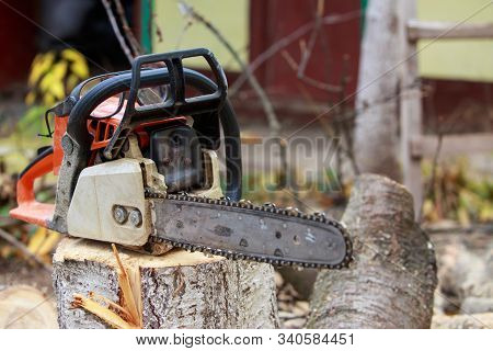 Chainsaw Stands On A Stump In The Open Air
