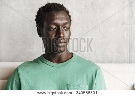 Image of perplexed serious african american man in casual clothes sitting on sofa at home