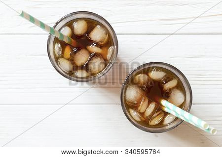 Black Tea, Coffee Or Cola With Ice And Paper Straw In Glass On White Wooden Background, Top View. Tw