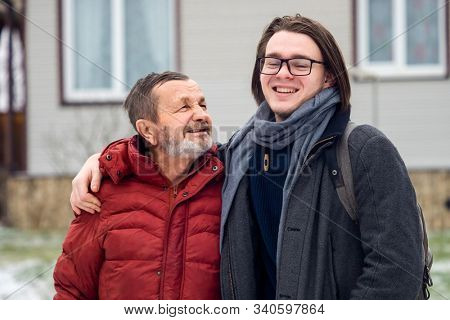Elderly man grandfather and his happy grandson teenager boy hugging outdoors in winter, family portrait in Russian village