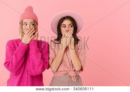 Image of two scared girls wearing girlish clothes expressing fright and covering their mouthes isolated over pink background
