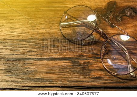 Single Simple Eye Glasses On The Wooden Table With Copy Space