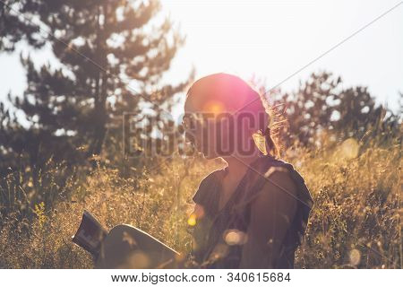 Woman Reading Book In Sunset. Lifestyle Concept. Hipster Woman Relaxing In Sunset In Meadow. Healthy