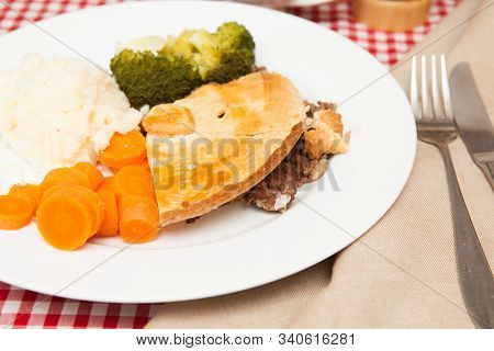 A Traditional British Meal Of Mincemeat Pie A Traditional Mincemeat Pie With Potato, Carrots, Brocco
