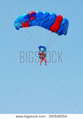 A Paratrooper In A Red Suit Descends Under The Canopy Of A Parachute