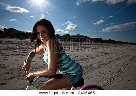 Young Brunette Woman Riding Bike On Beach