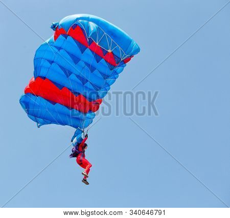 Paratrooper In Red Suit Descends Under Canopy Of Parachute