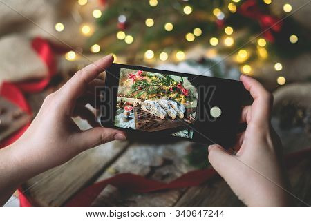 Woman Takes Photo On The Phone Of German Bread With Fir Tree Branches Decoration And Bokeh Lights.