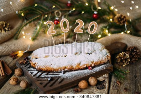 Homemade Traditional German Bread With Powdered Sugar And Inscription 2020 On Top - On Wooden Board