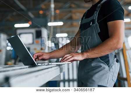 Modern Laptop. Typing On Keyboard. Industrial Worker Indoors In Factory. Young Technician With Orang
