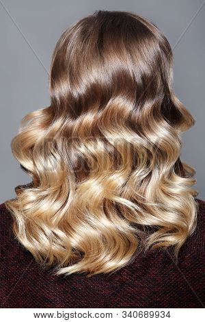 Beautiful And Shiny Curly Hair. Fashion Girl With Healthy Long Wavy Hair. Beauty Blonde Woman Back V