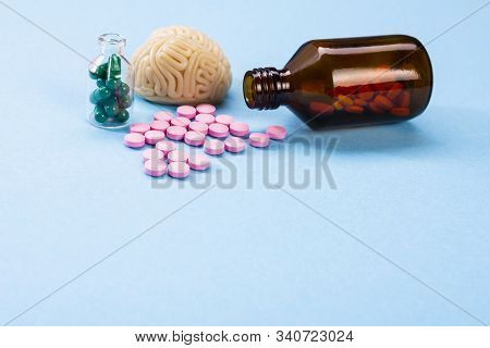 Brain On A Blue Background With Pink And Green Pills In A Glass Bottle. Some Pills For The Brain. Sy