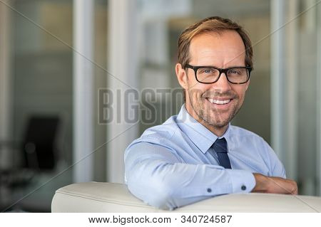 Portrait of mature businessman sitting on sofa in office lobby. Confident smiling man sitting on couch looking at camera. Happy executive manager wearing eyeglasses with copy space.