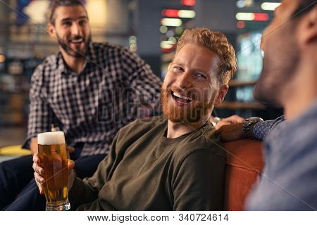 Group of laughing friends enjoying glass of draft beer together in a bar. Three mid adult men enjoying drinking at pub during night. Happy casual young man holding freshly brewed beer and laughing.