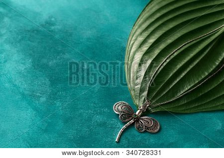 Silver Dragonfly Pendant On Turcuoise Background. The Chain Of Pendant Lies On Big Plant Leaf. Perfe