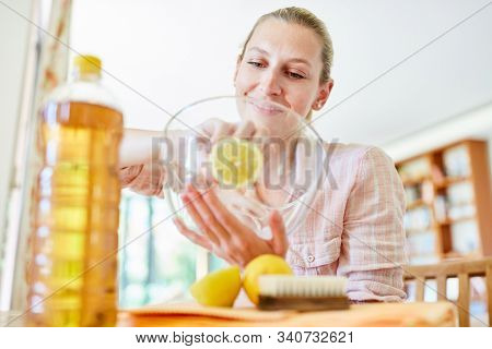 Housewife cleans glass bowl with citric acid as a cleanser and home remedy