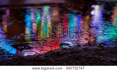 Colorful light is reflected in the puddle in the evening at a fair or fun fair