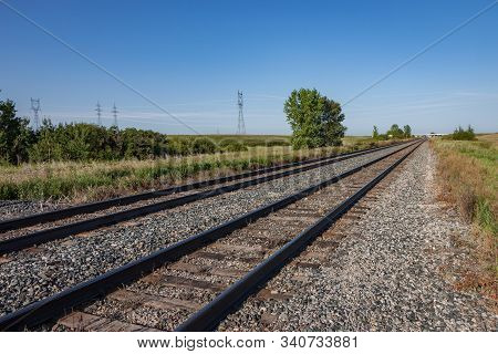 Two Pairs Of Empty Railroad Tracks On Canadian Prairie