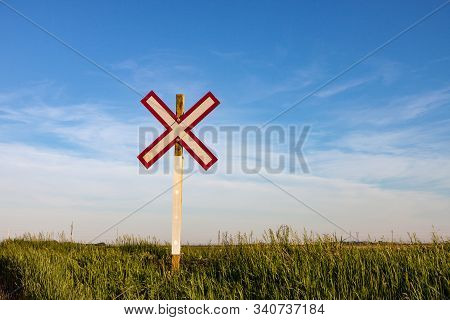 Lone Railroad Crossing Sign On Green Prairie Under Blue Summer Sky