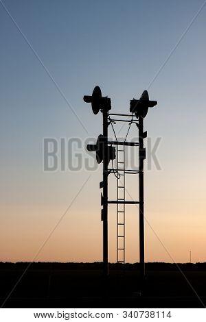 Railroad Traffic Signals Silhouetted Against Prairie Sunrise Sky