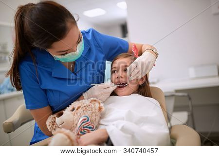 Dentist with dental mirror checkup child's teeth
