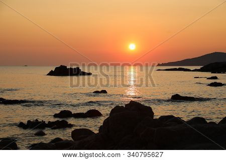 Red Sun At Sunset With Reflect On The Water Of Ocean