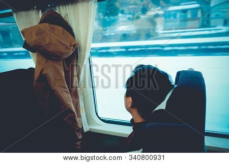 Asian Man Looking Through Window With Snow. He Travels On A Train In Hokkaido Japan. Concept Of Trav