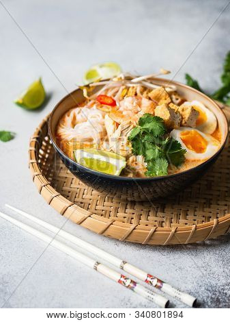 Malaysian Noodles Laksa Soup With Chicken, Prawn And Tofu In A Bowl On A Grey Background