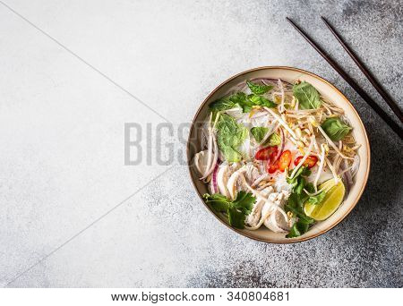 Traditional Vietnamese Soup- Pho Ga In Bowl With Chicken And Rice Noodles, Mint And Cilantro, Red On