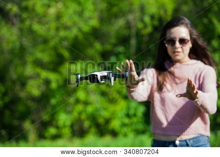 Walk With A Drone. A Young Woman In Black Glasses Launches A Low Flying Drone. Reaches Out To A Low