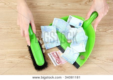 Sweeps money in the shovel on wooden background close-up
