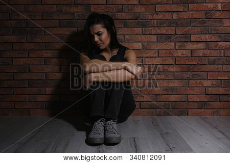 Abused Young Woman Near Brick Wall. Domestic Violence Concept