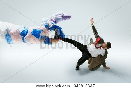 Young caucasian man avoiding big plastic hand on white studio background. Male model in office attire fighting in motion and action. Looks angry, scared, pressured. Eco problems, pollution, recycling. poster