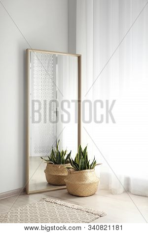 Large Mirror With Wooden Frame Near Window In Light Room