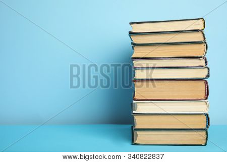 Stack Of Hardcover Books On Light Blue Background, Space For Text