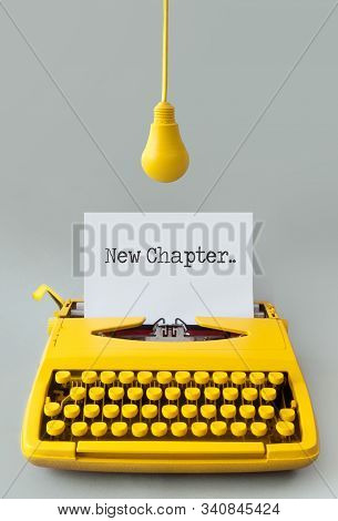 Retro Typewriter With Yellow Hanging Light Bulb, New Chapter